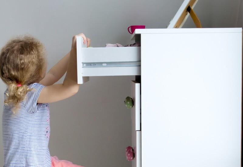 Young girl child climbing on modern high dresser furniture, danger of dresser dipping over concept. Children home hazards. Staged photo.